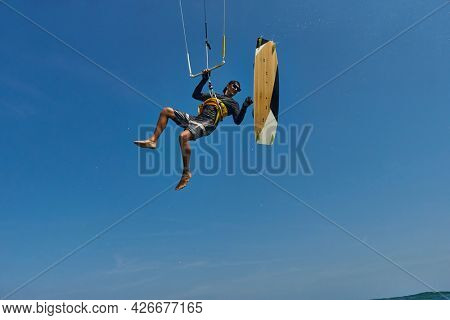 Kite surfer jumps with kiteboard  in transition and throws up the board