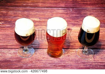 Three Glasses With Different Types Of Dark Beer Are On A Wooden Table.