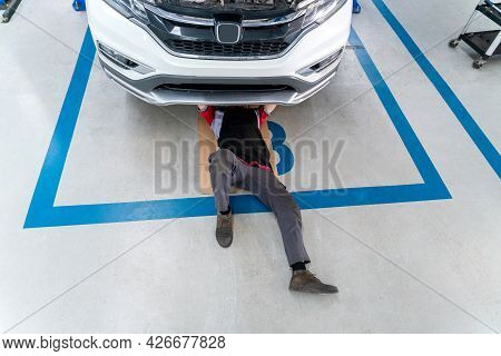 Top View Of Mechanic In Uniform Lying Down And Working Under Car, Car Mechanic Adjusting Tension In