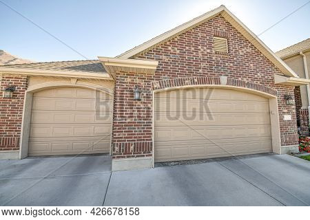 Detached Double Garage Exterior With Bricks And Concrete Driveway