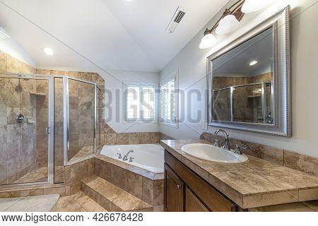 Traditional Bathroom Interior With Vanity And Corner Bathtub Against Jalousie Windows