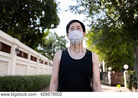 Young Asian Man Running With A Face Mask In The City. Male Runner Exercising And Jogging On The Stre