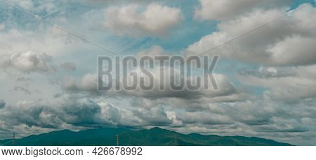 Panorama View Of The Overcast Sky Above The Green Mountain And Electric Pylons. Dramatic Sky And Cum