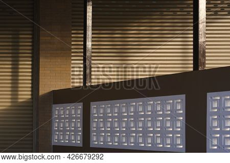 Sunlight And Shadow On Surface Of Roller Shutter Door Of Commercial Buildings Separated By A Concret
