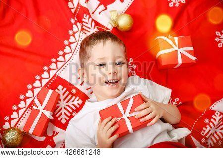 Little Boy Blonde Lying On The Floor. Cute Child Holding Xmas Gift. Santa Toddler Lying On His Back