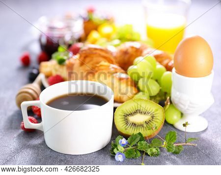 continental breakfast with coffee cup,  croissant,  orange juice