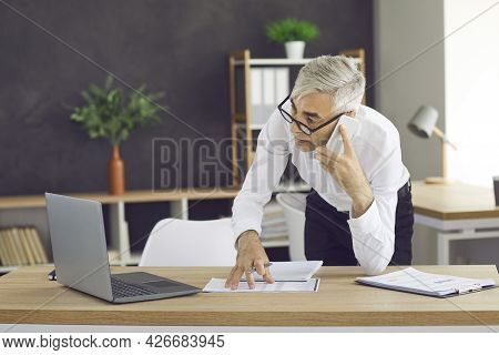 Businessman Talking On Cellphone In Contemporary Office.