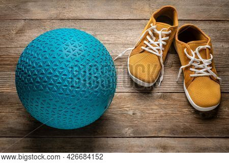 heavy rubber slam ball filled with sand on a rustic wooden deck with minimalist barefoot sneakers, exercise and fitness concept