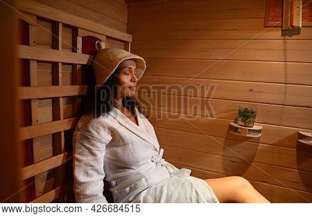 Serene Woman In Waffle Bathrobe And Sauna Hat Relaxing In Infrared Sauna. Spa Treatment, Alternative
