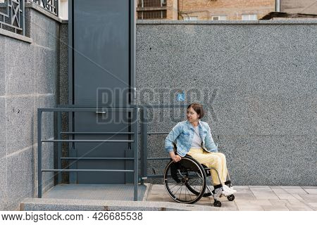 Mid aged smiling brunette disabled woman sitting in a wheelchair using accessible elevator for disabled persons