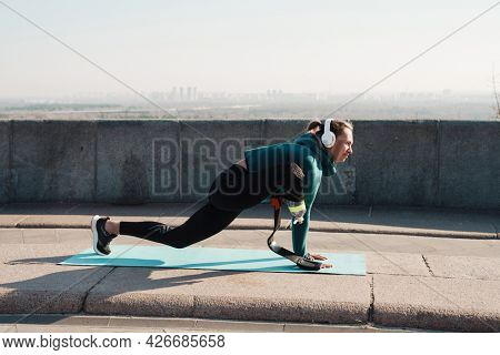 Young sportswoman with prosthesis doing exercise while working out on city bridge stretching