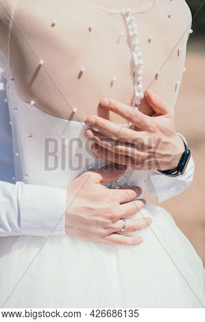 The Groom Hugs The Bride. Vertical Photo Of The Bride And Groom. Beautiful Buttons On The Brides Bac