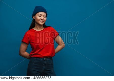 Portrait of a happy casual young asian woman wearing hat standing over blue wall background eyes shut