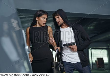 Angry robber grabbing hand of frightened girl and threatening with pistol. Bottom view of european male bandit want to steal handbag of young brunette woman. Concept of robbery. Inside parking lot
