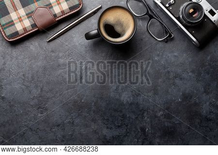 Office desk table with camera, supplies and coffee. Dark workspace tabletop with copy space. Top view flat lay