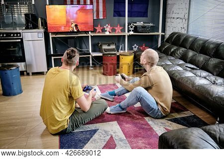 Friends enjoying playing videogame together when sitting on the floor of living room