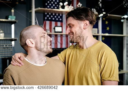 Two young affectionate gay men embracing and looking at each other