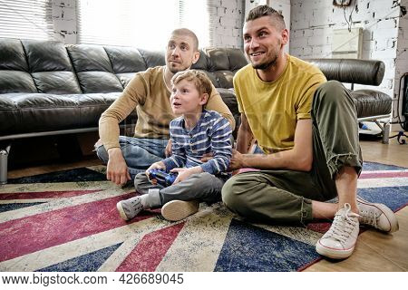 Two happy fathers supporting their little son playing videogame on console