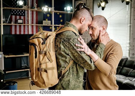Military man in uniform hugging his boyfriend and promising to come back after military exercises