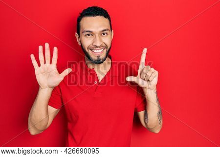 Hispanic man with beard wearing casual red t shirt showing and pointing up with fingers number seven while smiling confident and happy.