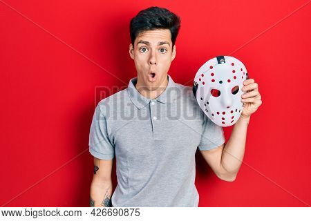 Young hispanic man wearing hockey mask scared and amazed with open mouth for surprise, disbelief face
