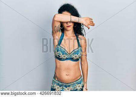 Young woman wearing bindi and traditional belly dance clothes covering eyes with arm, looking serious and sad. sightless, hiding and rejection concept