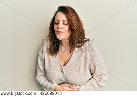 Young caucasian woman wearing casual clothes with hand on stomach because indigestion, painful illness feeling unwell. ache concept.