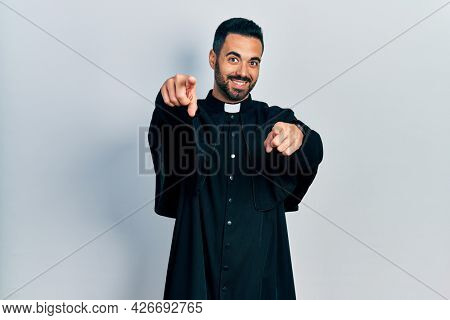 Handsome hispanic man with beard wearing catholic priest robe pointing to you and the camera with fingers, smiling positive and cheerful