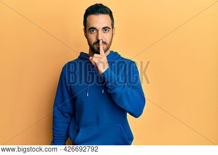 Young hispanic man wearing casual clothes asking to be quiet with finger on lips. silence and secret concept.