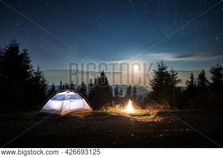 White Tourist Tent Locating On Mountain Hill Near Burning Campfire At Forest. Moonlight In The Magic