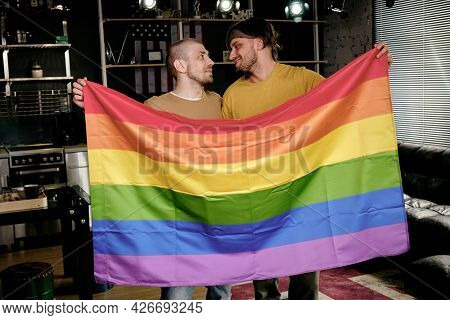 Young affectionate homosexual men holding rainbow flag and looking at each other when standing in apartment