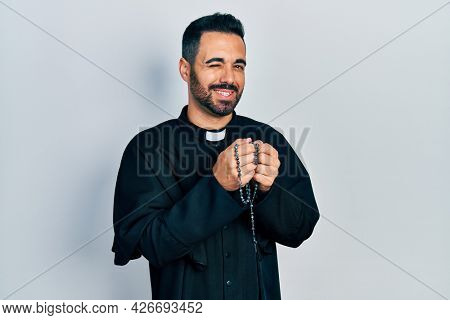 Handsome hispanic priest man with beard praying holding catholic rosary winking looking at the camera with sexy expression, cheerful and happy face.