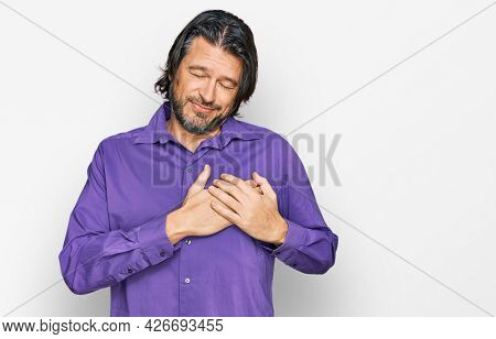 Middle age handsome man wearing business shirt smiling with hands on chest with closed eyes and grateful gesture on face. health concept.
