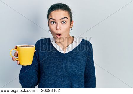 Young caucasian girl holding coffee scared and amazed with open mouth for surprise, disbelief face