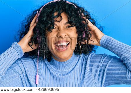 Young hispanic woman listening to music using headphones smiling and laughing hard out loud because funny crazy joke.