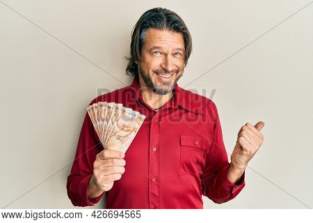 Middle age handsome man holding 50 turkish lira banknotes pointing thumb up to the side smiling happy with open mouth