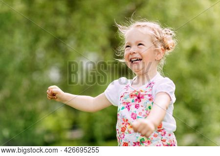Happy Laughing Baby Girl Running In A Clover Fielda Happy Laughing Baby Is Running Around The Park O