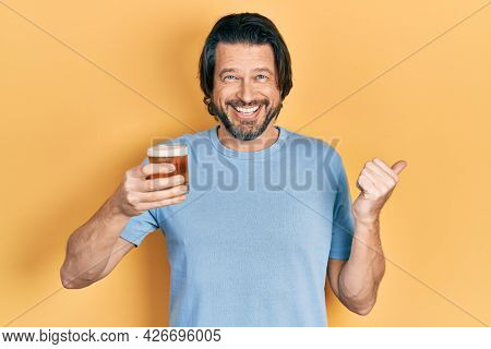 Middle age caucasian man drinking a pint of beer pointing thumb up to the side smiling happy with open mouth