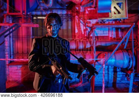 Courageous action hero with automatic guns in an industrial zone at night. Handsome wounded man special agent.