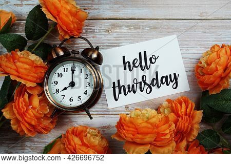 Hello Thursday Card And Alarm Clock With Orange Flower Decoration On Wooden Background