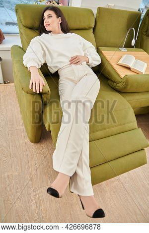 Beautiful brunette woman having a rest on a sofa in her cozy living room. Happy life, happy people concept.