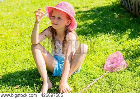 A Little Girl Sits On Fresh Grass And Holds A Caught Butterfly In Her Hands.