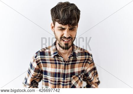 Hispanic man with beard standing over isolated background with hand on stomach because indigestion, painful illness feeling unwell. ache concept.