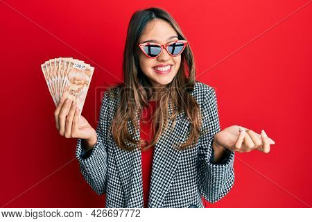 Young brunette woman holding 50 turkish lira banknotes celebrating achievement with happy smile and winner expression with raised hand