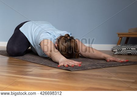 Pregnant Yoga Woman Working Out In Living Room In Prenatal Balasana, Child Pose