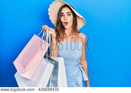 Young hispanic girl holding shopping bags scared and amazed with open mouth for surprise, disbelief face