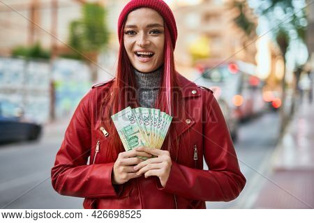 Young caucasian girl smiling happy holding russian ruble banknotes at the city.