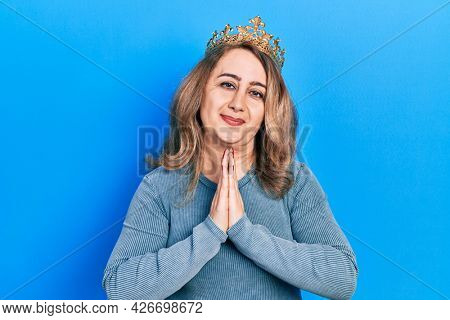 Middle age caucasian woman wearing queen crown praying with hands together asking for forgiveness smiling confident.