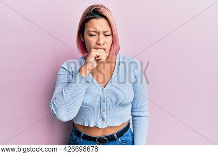 Hispanic woman with pink hair standing over pink background feeling unwell and coughing as symptom for cold or bronchitis. health care concept.