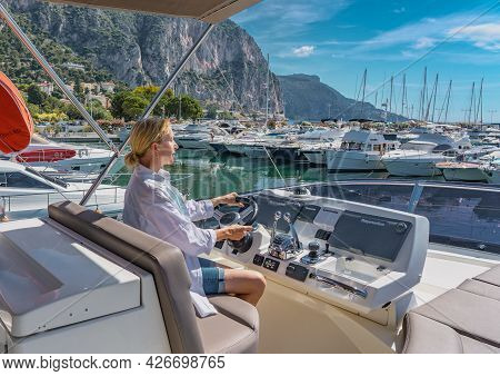 Beaulieu -sur-mer, France - 26.06.2021: Beautiful Blond Woman Driving Yacht. Adult Woman Model In A